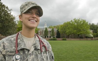Cadet Stafford smiling for the camera in Moffett Quad with her stethoscope around her neck
