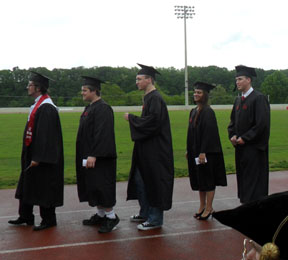 Physics grads wait in the rain to walk across the stage.