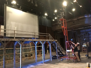 Professor David Wheeler and students adjust lights on the stage of Pridemore Playhouse