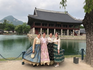 Dance students pose in traditional Korean attire at edge of lake.