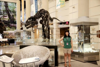 Graphic design student Ling Jie Gu poses beside an allosaurus skeleton at the Virginia Museum of Natural History