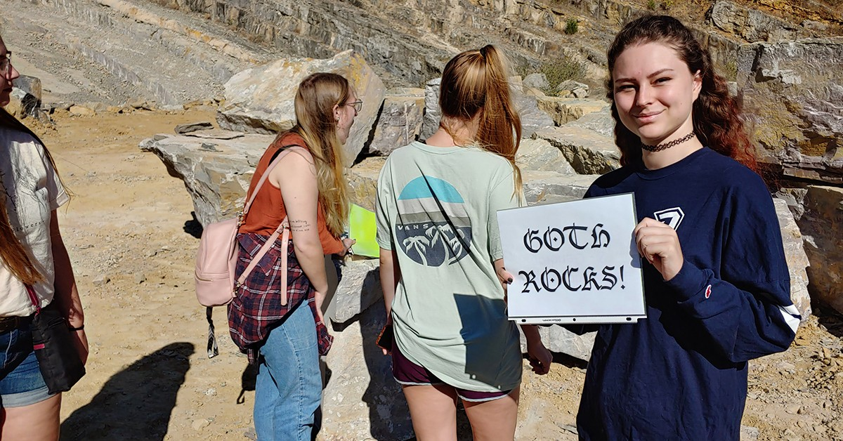 "Students hold a sign that reads ""goth rocks"" while visiting Virginia Tech's rock quarry"