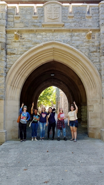 Students in the gothic architecture class pose under cow gargoyles at Virginia Tech