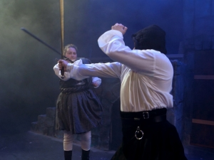 Students perform a sword-fight sequence on stage during a rehearsal of Macbeth