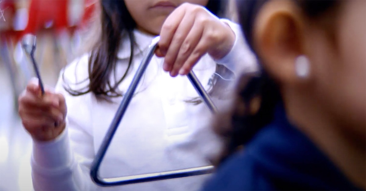 A child plays triangle during a music activity in school