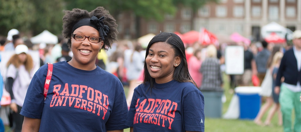 Two students wearing Radford University shirts and smiling