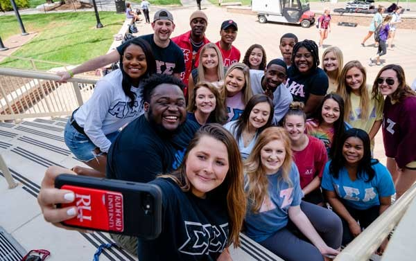 Students wearing their Greek letters pose for a group selfie.