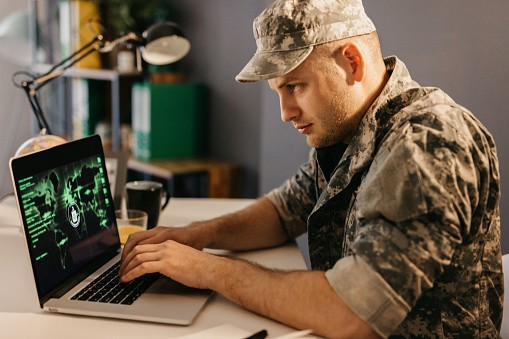 Military serviceman working on a laptop
