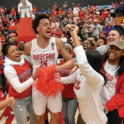 The Radford University men's basketball team celebrates after a win in the NCAA