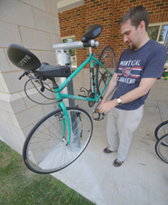 Geoff White works on his bike on one of the new bike repair stands outside of Hurlburt Hall.