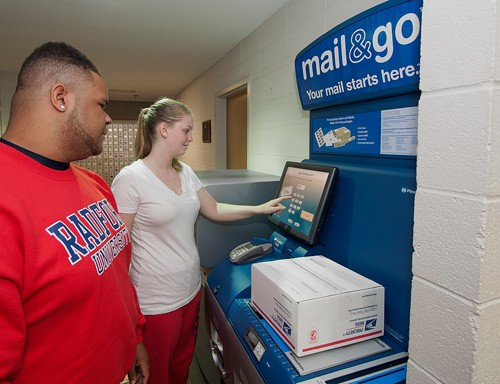 Emily Gerding and Ezell Johnson weigh a package on the new Mail & Go kiosk at the RU Post Office.