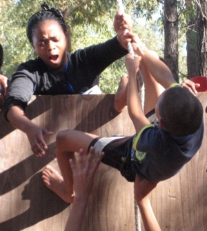 A trainer with Resilient Kids SA helps a camper over an obstacle