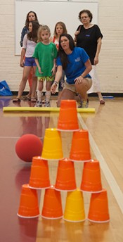 Leda takes a turn at knocking down a pyramid of cups as part of the Carnival activities