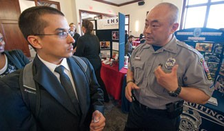Criminal Justice major Tristan Lora talks with Fairfax Police Department's Roy Choe