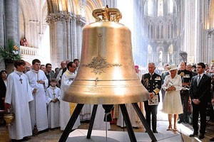 In theAt a christening ceremony in nave of Normandy's Bayeux Cathedral, Great Britain's Queen Elizabeth served as senior godparent while Sperry Grills, a junior godparent, looked on.