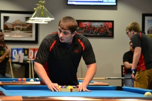 Radford University Billiards Club members Jessie Fitzgerald (center) and Brad Egener (left) compete in the March 24-25 pool tournament, hosted by the university, on March