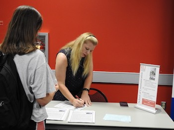 Associate Professor Lisa Baker Webster, center, explains the offerings in the School of Communication to a student.
