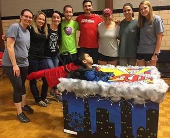 RU DPT second-year students celebrate the reveal of their assistive trick or treat costume they created for the Hallowheels competition with its recipient.