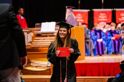 A Radford University student smiles after walking across the stage at Winter Commencement.
