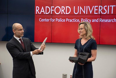 Roberto Santos (left) and Rachel Santos (right) announce the inaugural Excellence in Policing Award recipient.