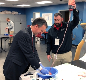 "U.S. Rep. Ben Cline receives hands-on education in how to apply a tourniquet to slow bleeding in ""The Emergency Experience."""