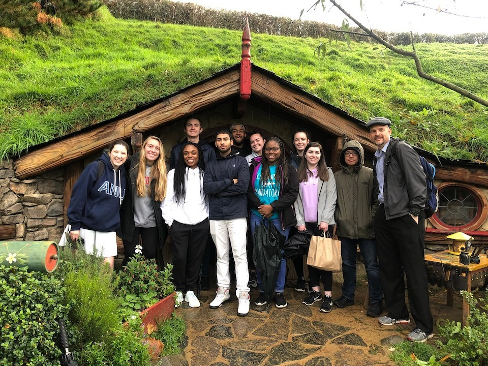 "The study abroad group visited the set of the movie trilogy ""The Lord of the Rings"" and is pictured in front of a Hobbit Hole in Hobbiton."