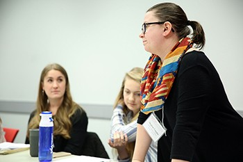A student leads her group's discussion and takes notes at the IPE symposium.