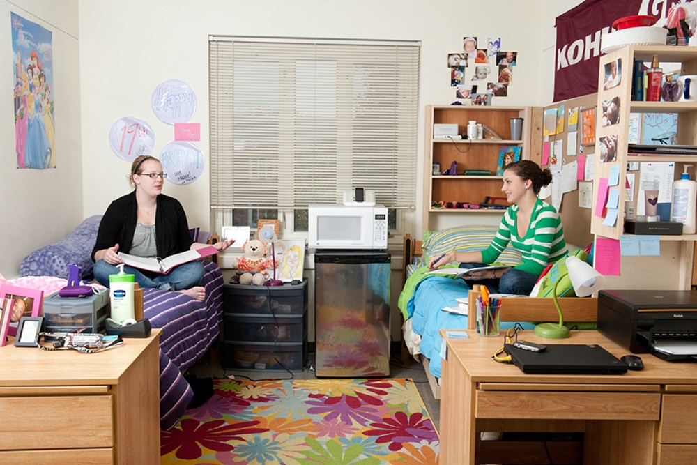 Two female roommates sitting in their beds, talking and doing work